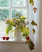Autumnal bouquet of leaves and rose hips in window