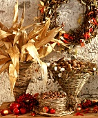 Wicker basket with maize leaves, nuts & autumn decoration
