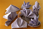 Fans, lilies and boats made from folded fabric napkins
