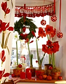 Red & white Xmas window decoration with plants, candles etc.