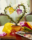 Flowerpot with heart-shaped plant and paper hearts