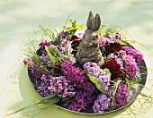 Blumenarrangement mit Flieder und Osterhase auf einem Teller