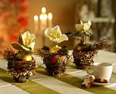 Drei weihnachtlich dekorierte Tontöpfchen als Tischdeko