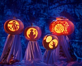 Four carved pumpkins with creepy motifs
