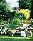 Pure relaxation: table and lounger on lawn by garden pond