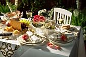Gedeckter Tisch mit Rosenblüten, Käseplatte, Oliven etc.