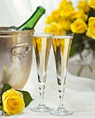 Two glasses of champagne, champagne bucket with bottle & roses