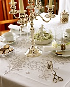 Table laid for coffee with silver chandelier