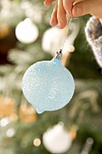 Child's hand holding a pale-blue Christmas bauble