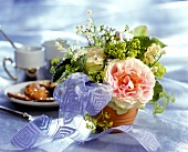 Delicate table arrangement of lilies of the valley and roses