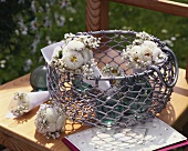 Metal basket with small bouquets of white flowers