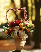 Tannengesteck mit Rosen und Ericaherz im Tontopf