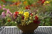 Summer arrangement of flowers and grasses in wicker bowl