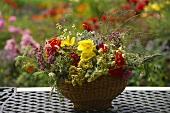 Sommerliches Gesteck mit Blüten und Gräsern in Korbschale