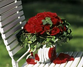 Bouquet of red roses on a garden chair