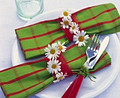 Two napkins in napkin rings with marguerites
