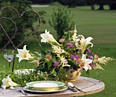 Laid table with arrangement of lilies, astilbe and Ageratum