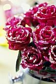 Rote Rosen mit Silberblättchen bedeckt in einem Sektkübel
