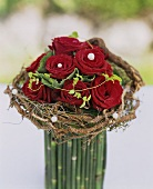 A bouquet of roses surrounded by a wreath of twigs