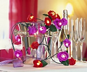 String of flower lights with champagne cooler and glasses