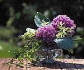Zwei Alliumblüten, Funkienblättern & Efeu in einer Glasvase