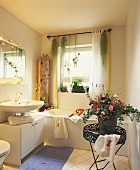 View into bathroom with flower arrangement on tray table and plants in window