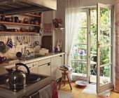 Blick von der Küche durch offene Glastür auf kleine Terrasse