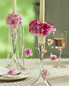 Candlestick with candle ring of pink silk flowers