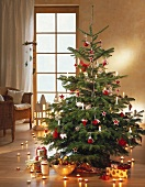 Decorated Christmas tree with presents and row of tea lights on parquet flooring