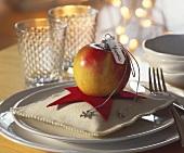 Apfel mit Platzkärtchen auf kleinem Sternkissen