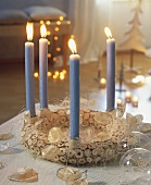 Christmas wreath made of wooden discs with 4 pale-blue candles
