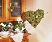 White rose in pot & Gerbera on sideboard, moss heart with arrow