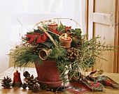 Advent arrangement of poinsettia, juniper and candles