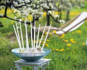 A bowl with ten candles and flowers standing in open air