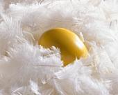 Gelb gefärbtes Ei zwischen weissen Federn