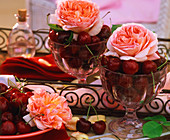 Fragrant English roses with cherries in glasses