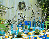 Laid table with blue bottles and olive branches