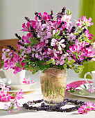 Various scented pelargoniums and lavender in a glass vase