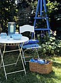Garden furniture and a picnic basket in grass
