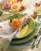 Festive table setting with green plates and roses