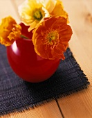 Flowers in a red vase on table cover on wooden table