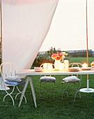 Tisch unter Zelt mit Kerzen und Blumen bei Abendstimmung
