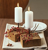 Table decoration: white candles and branch of rose hips