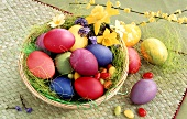 Easter eggs and sugar eggs in basket; spring flowers