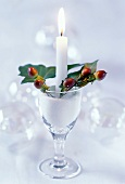 Festive table decoration with candle & rose hips in wine glass