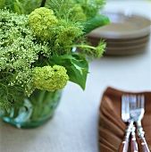 Posy of green flowers beside brown napkins and forks