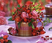 Small posy of roses and rose hips in coffee cup