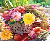 Autumn table decoration of dahlias, cereal ears, apples & pears