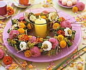 Wreath of zinnias around wind light with yellow candle