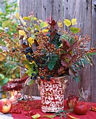 Vase of rose hips, sloes and autumn leaves